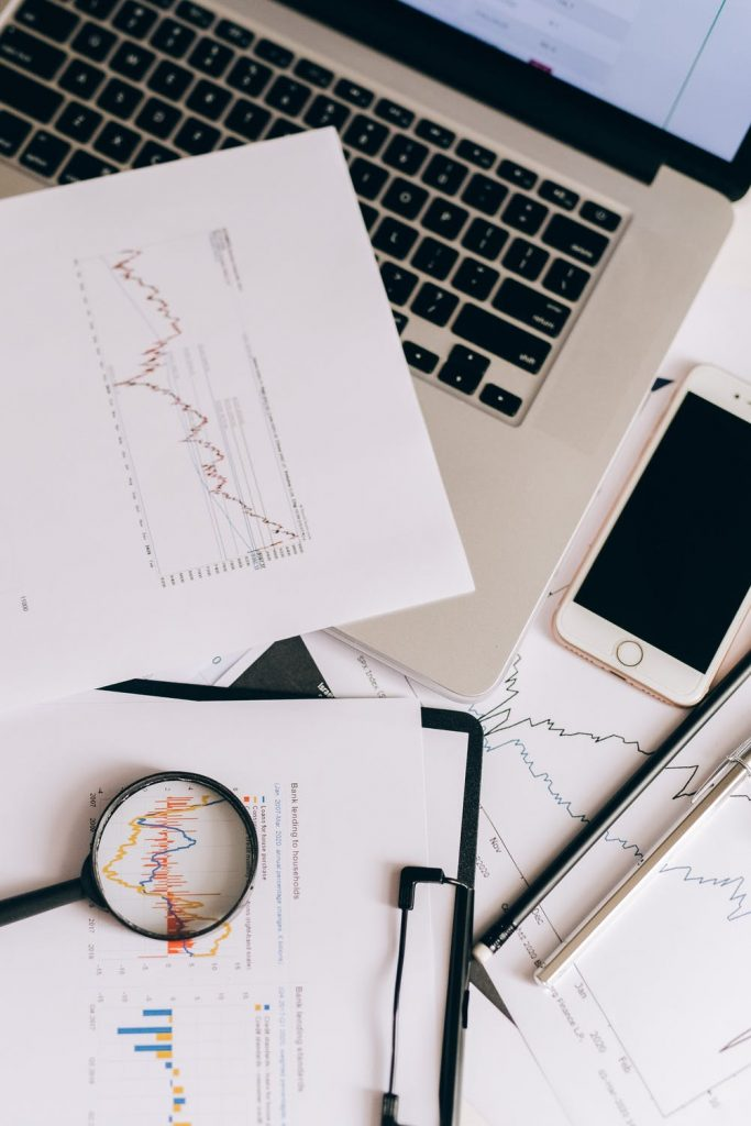 Papers with graphs and statistics on a table next to a laptop and an iPhone
