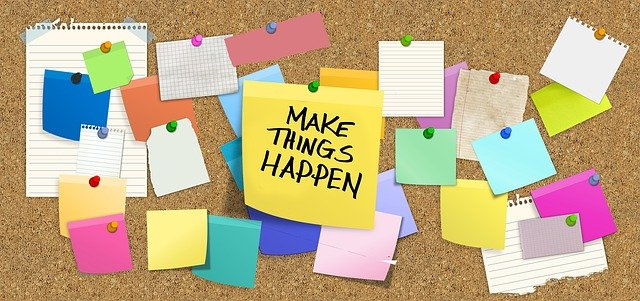 """A board with pinned notes, where a central yellow note spells """"Make things happen."""